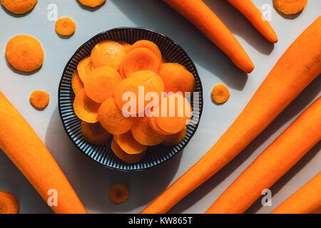 Peeled and Sliced Carrots on Grey Table - Stock Photo