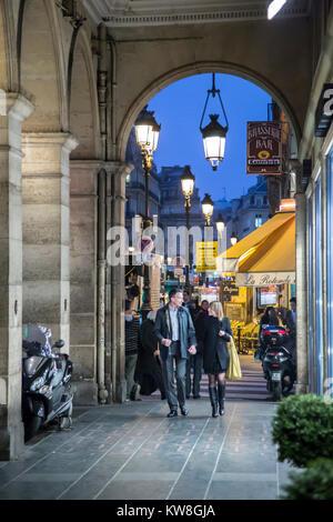 France, Paris (75), Couple walking under colonnade along Rue des Pyramides - Stock Photo