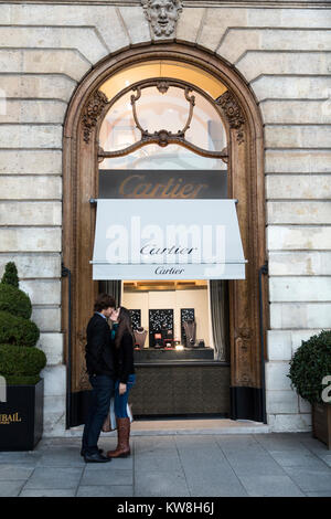 A couple kissing in front of Cartier's store in Place Vendome, Paris, France - Stock Photo