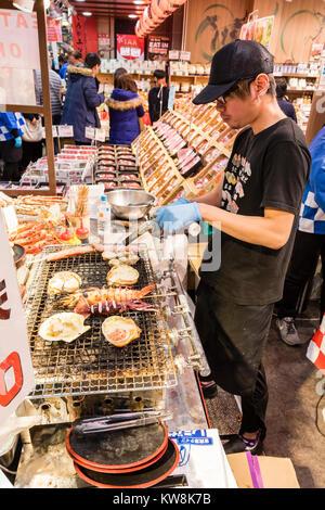 Japan, Osaka, Kuromon Ichiba Market, Osaka, Fish food stall, view along, as young man cooks shell fish with blow - Stock Photo