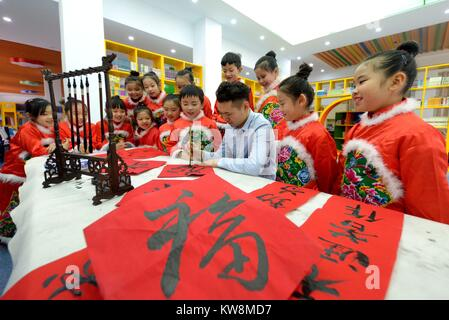 Shijiazhuang. 31st Dec, 2017. A teacher shows primary school students Chinese calligraphy during an extracurricular - Stock Photo