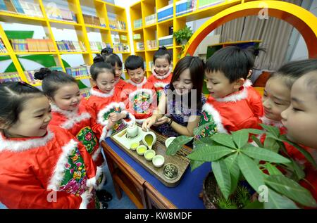 Shijiazhuang. 31st Dec, 2017. A teacher shows primary school students the tea ceremony during an extracurricular - Stock Photo