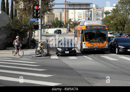 Mother & child on bikes wait for traffic and bus to cross the road at traffic lights on Rowena Ave Silver Lake, - Stock Photo
