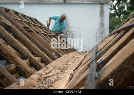 Carpenter working on roof of school, Tamil Nadu, South India. Beams are made of wood from the palmyra palm. - Stock Photo