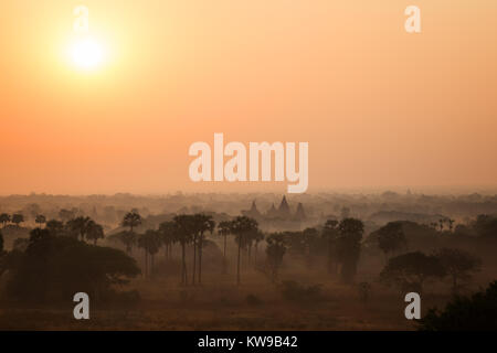Sunrise over misty plain and ancient temples in Bagan, Myanmar (Burma). - Stock Photo