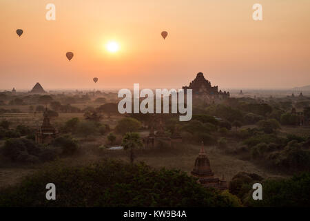 Silhouette of many ancient temples and pagodas and four hot-air balloons over plain of Bagan in Myanmar (Burma) - Stock Photo