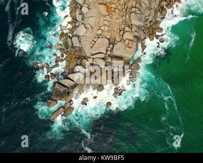 Waves breaking against rock formations on the beach - Stock Photo