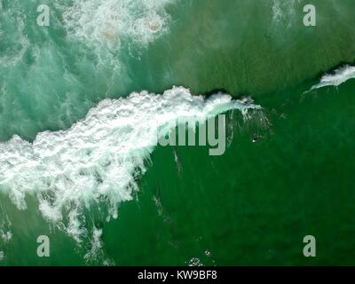 surfer swimming around a wave breaking seen from above - Stock Photo
