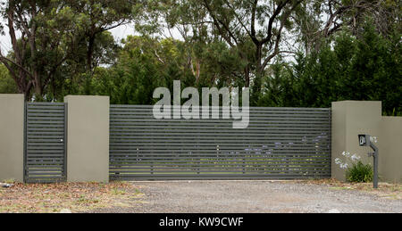 Metal driveway entrance gates set in brick fence leading to rural property with eucalyptus trees in background - Stock Photo