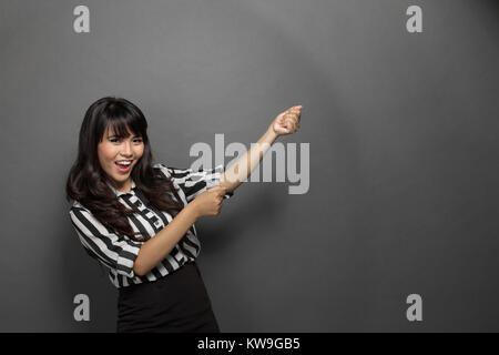 portrait of a young businesswoman pulling out something - Stock Photo