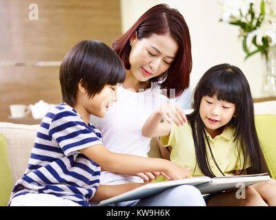 young asian mother and her son and daughter sitting on couch reading a book together. - Stock Photo