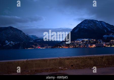 daybreak illuminates the lake of Lugano and the surrounding mountains - Stock Photo