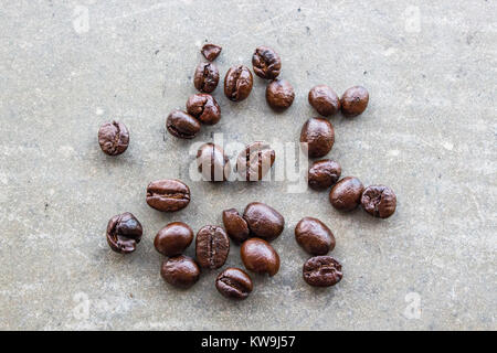 Close up of coffee beans on concrete floor. Top view of brown coffee bean on concrete table. - Stock Photo