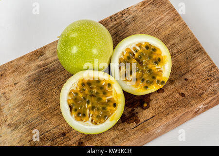 A group of  passion fruit in a wood, two halves of a maracuya fruit, with the dough and the seeds in sight - Stock Photo