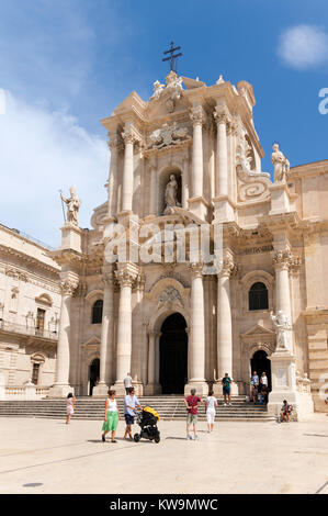 A young couple pushing a buggy outside Syracuse cathedral in the Piazza Duomo, Sicily, Europe - Stock Photo