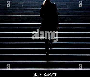 Urban walk : Blurry silhouette of young elegant woman climbing up the city street public stairs in the winter, alone - Stock Photo