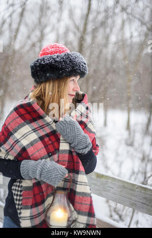 happy woman walking outside in woods while snow is falling holding lantern - Stock Photo