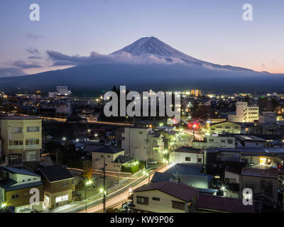 A long exposure of Mt fuji taken in a town near Lake Kawaguchiko with light trails of cars at the bottom in the - Stock Photo