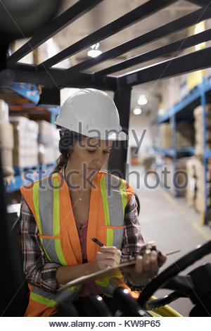 Female worker with clipboard driving forklift in distribution warehouse - Stock Photo