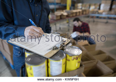 Male volunteer with clipboard managing food drive in warehouse - Stock Photo