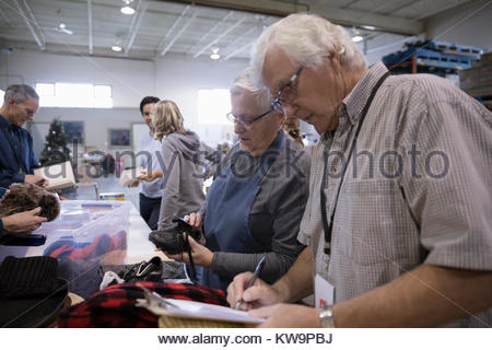 Senior couple with clipboard at clothing drive in warehouse - Stock Photo