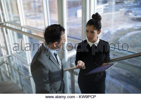 Businessman and businesswoman with digital tablet talking on office stairs - Stock Photo