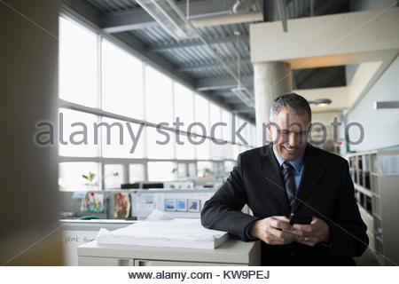 Smiling mature male architect texting with smart phone in office - Stock Photo