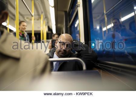 Tired mature businessman commuter sleeping on bus - Stock Photo
