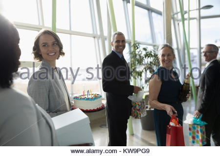 Happy business people carrying birthday cake and gifts in office - Stock Photo