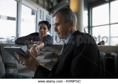 Businessman and businesswoman talking,using digital tablet in office - Stock Photo