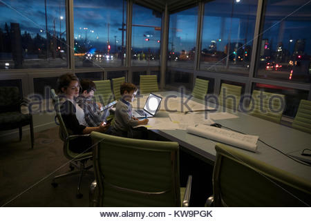 Dedicated mother architect working late with sons coloring in dark conference room - Stock Photo