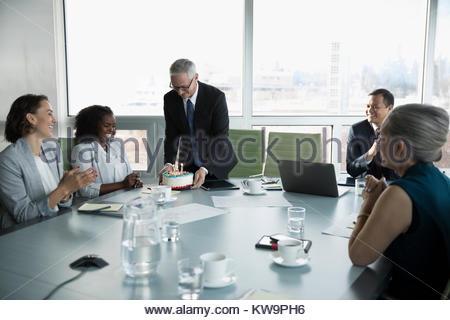 Businessman serving birthday cake to happy businesswoman in conference room - Stock Photo