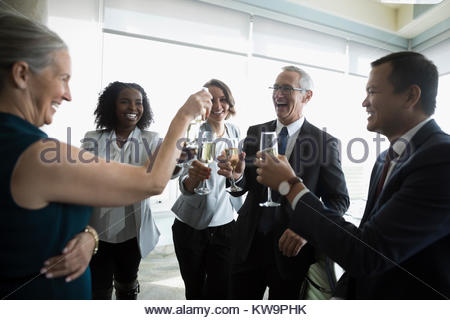 Happy business people celebrating,toasting champagne glasses in conference room - Stock Photo