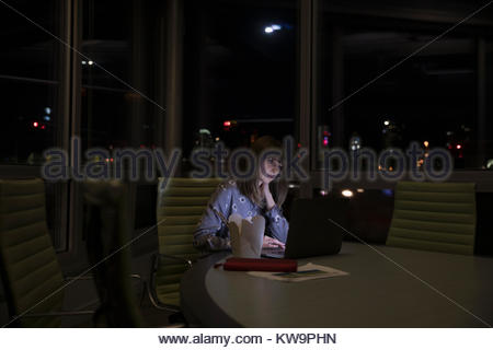 Dedicated businesswoman working late,eating takeout at laptop in dark conference room - Stock Photo