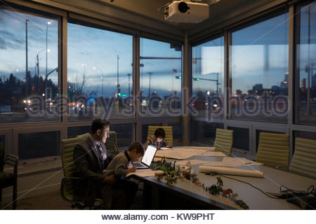 Dedicated father architect working late at laptop with sons playing in conference room - Stock Photo