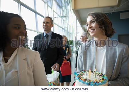 Happy businesswomen with birthday cake in office - Stock Photo