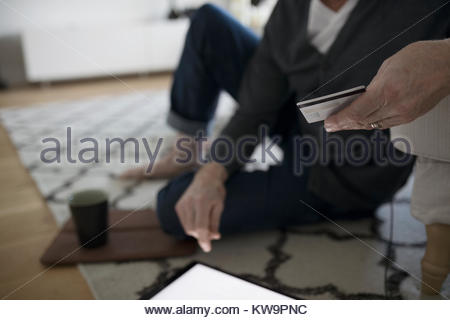 Close up senior man online shopping with digital tablet and credit card - Stock Photo
