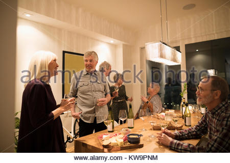Senior friends talking,enjoying wine tasting party social gathering in dining room - Stock Photo