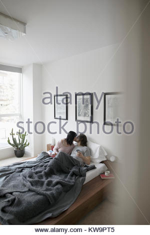 Affectionate,romantic couple kissing in bed - Stock Photo