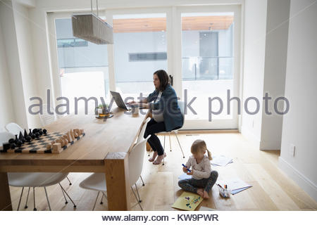 Pregnant mother working at laptop near toddler daughter playing on dining room floor - Stock Photo