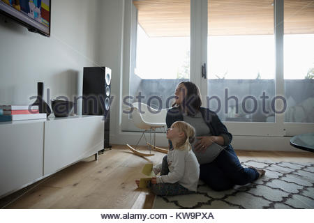Pregnant mother and toddler daughter watching TV on living room floor - Stock Photo
