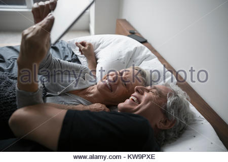 Affectionate,happy senior couple taking selfie with digital tablet,cuddling in bed - Stock Photo