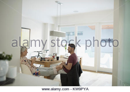 Affectionate couple in pajamas relaxing and drinking coffee at dining table - Stock Photo