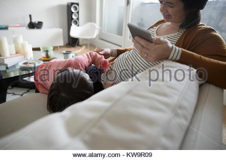 Toddler daughter touching pregnant mother - Stock Photo
