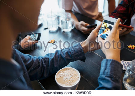 Tween boy using camera phone and drinking coffee at cafe table - Stock Photo