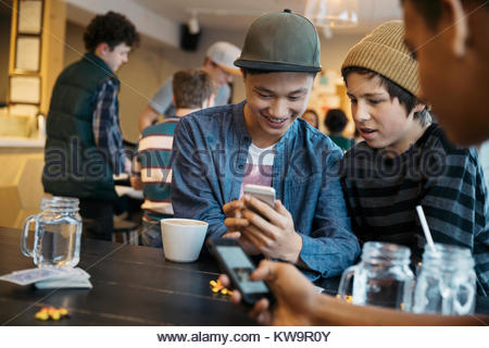 Tween boy friends texting with smart phone at cafe table - Stock Photo