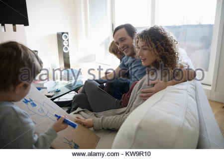 Family relaxing on sofa,son showing parents drawing on cardboard - Stock Photo