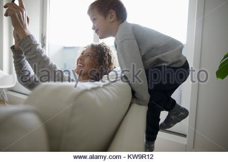 Playful mother and son taking selfie with digital tablet on sofa - Stock Photo