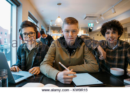 Portrait confident high school boy students studying,using stylus on digital tablet in cafe - Stock Photo