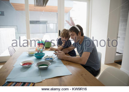 Father in costume rabbit ears and son texting with smart phone and dyeing Easter eggs at table - Stock Photo